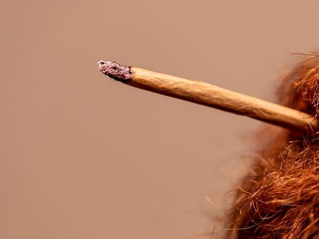Mężczyzna z czerwoną brodą pali jointa.