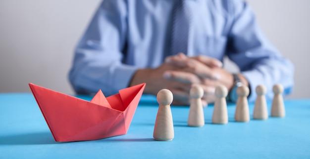 Mężczyzna z czerwoną łódką z papieru origami i ludzkimi drewnianymi figurami. biznes, przywództwo