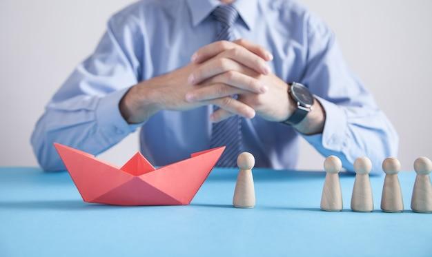 Mężczyzna z czerwoną łódką z papieru origami i ludzkimi drewnianymi figurami.