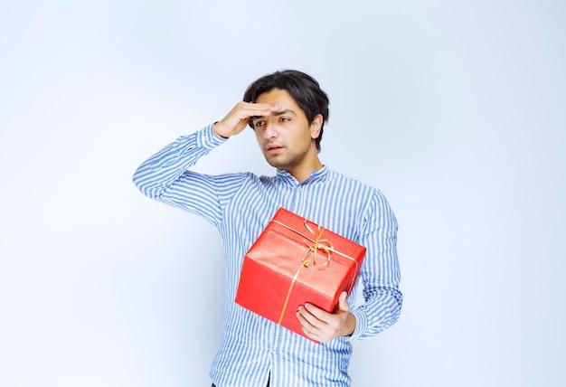 Mężczyzna z czerwonym pudełkiem wygląda na zmęczonego i znudzonego. zdjęcie wysokiej jakości