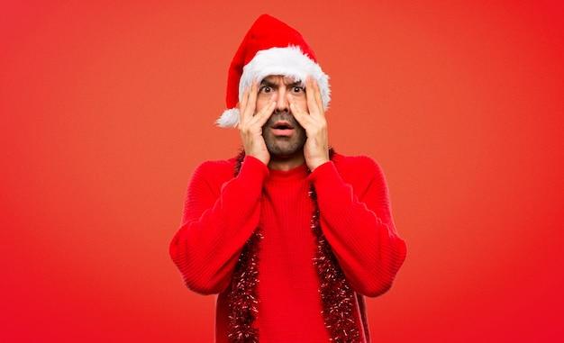 Mężczyzna z czerwonymi ubraniami obchodzi święta bożego narodzenia zaskoczony i obejmujące twarzy