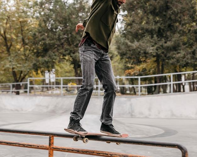 Mężczyzna z deskorolką na zewnątrz w parku miejskim