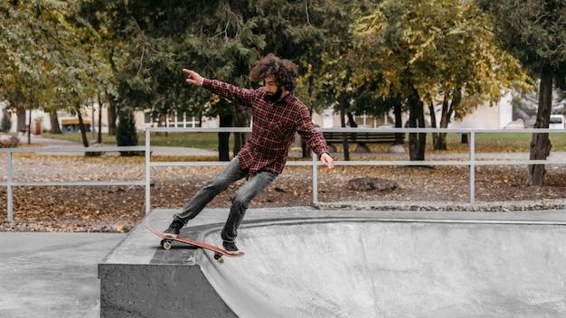 Mężczyzna z deskorolką na zewnątrz w parku