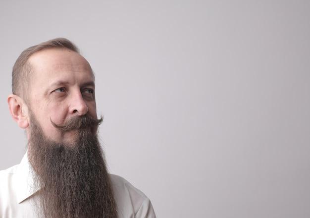 Mężczyzna z długą brodą i wąsami stojący przed szarą ścianą