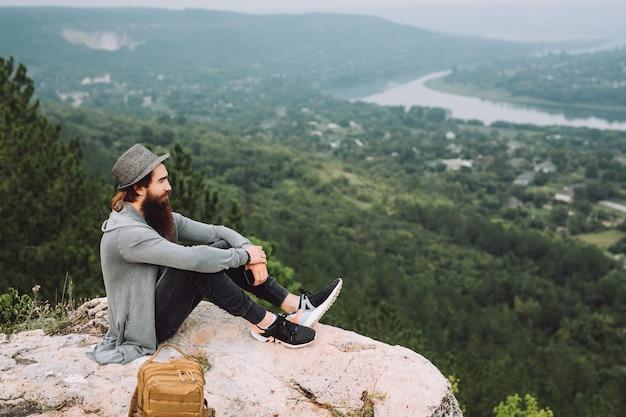 Mężczyzna z długą brodą siedzący na szczycie góry