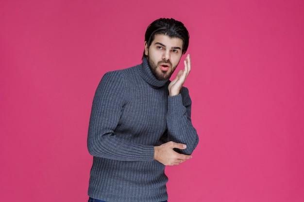 Mężczyzna z długimi włosami i brodą otwiera ręce i wygląda na zdezorientowanego lub niedoświadczonego.