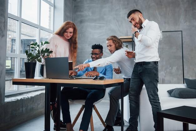 Mężczyzna z długimi włosami pokazuje, co robić w laptopie. grupa wielorasowych pracowników biurowych w formalnych ubraniach rozmawiających o zadaniach i planach