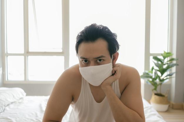 Mężczyzna z długimi włosami w higienicznej masce jest znudzony kwarantanną