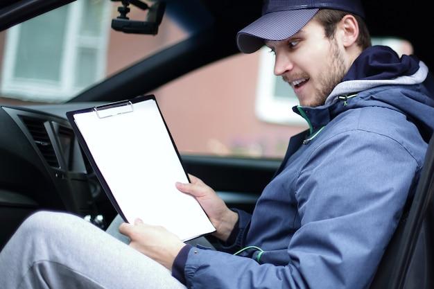 Mężczyzna z dokumentami siedzi w samochodzie