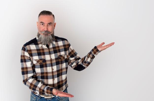 Mężczyzna z dużą brodą i wąsami koszuli w kratę z rękami skierowanymi w bok