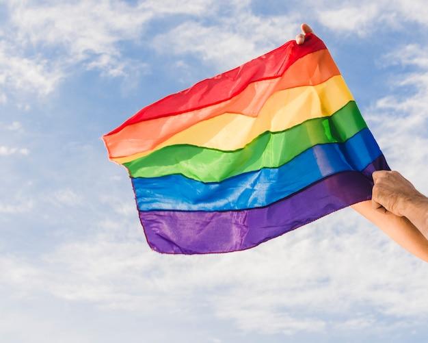 Mężczyzna z dużą flaga w lgbt kolorach i niebieskim niebie z chmurami