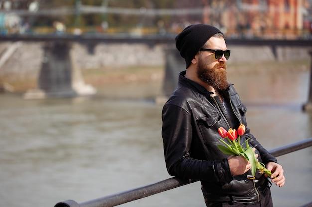 Mężczyzna z dużą krzaczastą brodą w ciepłej czapce i okularach przeciwsłonecznych w skórzanej kurtce i ciemnych spodniach stoi z czerwonymi tulipanami na tle kładki dla pieszych i rzeki