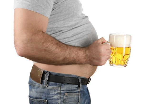 Mężczyzna z dużym brzuchem trzyma szklankę piwa na białym tle