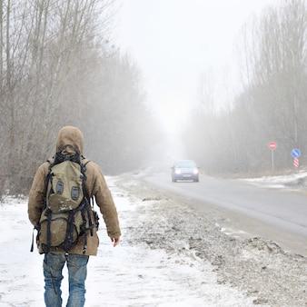 Mężczyzna z dużym plecakiem idzie podmiejską asfaltową drogą