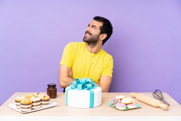 Mężczyzna z dużym tortem nad odosobnioną ścianą