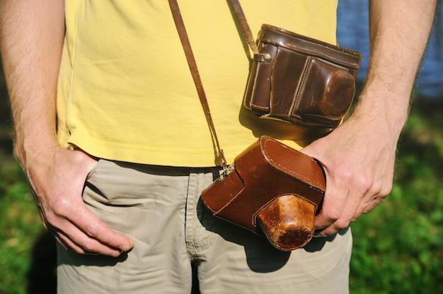 Mężczyzna z dwoma aparatami fotograficznymi w stylu vintage w skórzanych etui