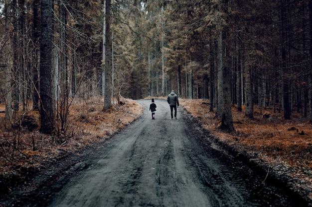 Mężczyzna z dzieckiem idący drogą otoczoną lasem porośniętym drzewami