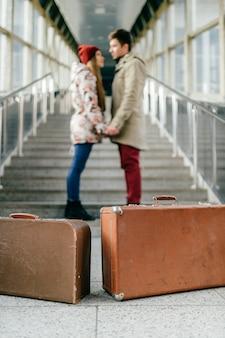 Mężczyzna z dziewczyną, walizki czekają na pociąg na schodach.