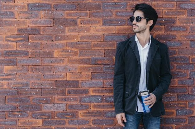 Mężczyzna z filiżanką blisko ściana z cegieł