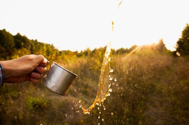 Mężczyzna z filiżanką bryzga wodę w powietrzu