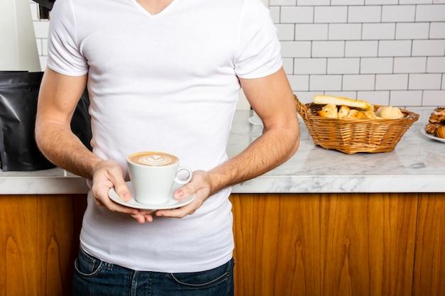 Mężczyzna z filiżanką cappuccino w jego rękach