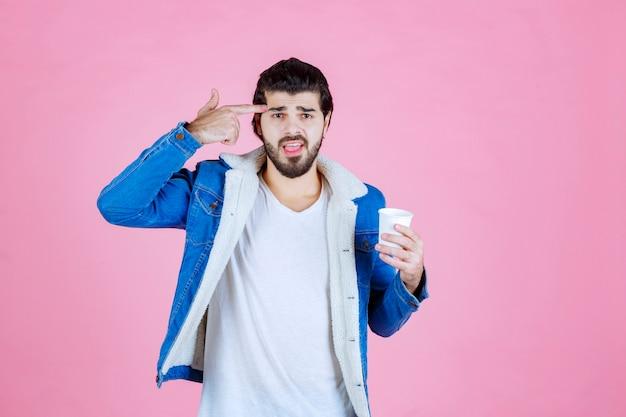 Mężczyzna z filiżanką kawy wskazującą na jego głowę