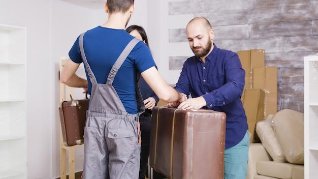 Mężczyzna z firmy kurierskiej przybywający z walizkami młodej pary do nowej nieruchomości. para przeprowadzka do nowego mieszkania.
