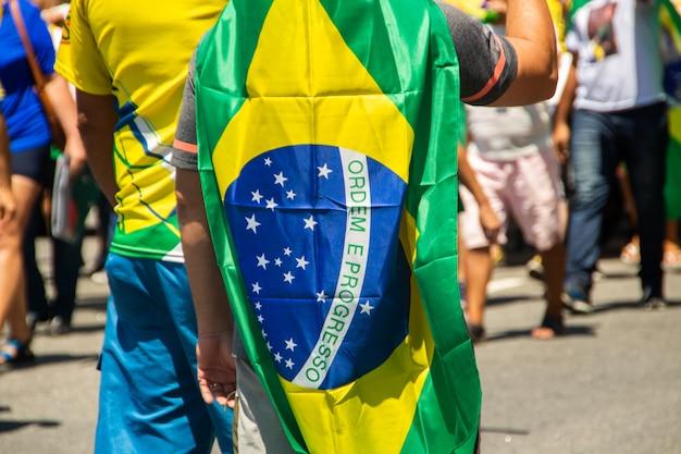 Mężczyzna z flagą brazylii podczas marszu w rio de janeiro