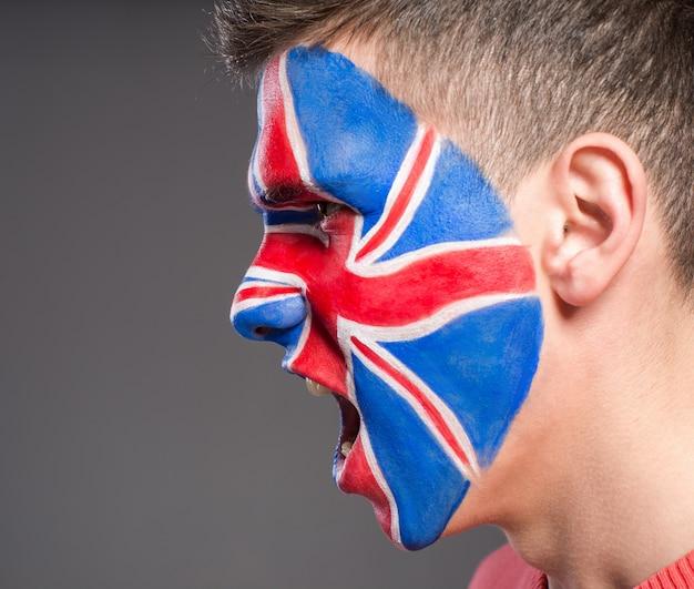 Mężczyzna z flagą na twarzy wspiera zjednoczone królestwo w sporcie.
