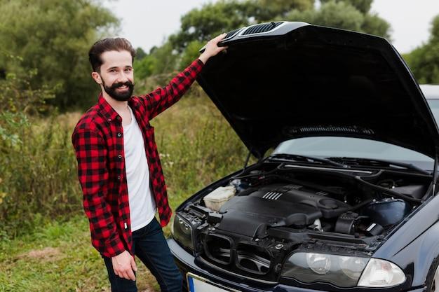 Mężczyzna z flanelową koszulą i otwartym kapturem samochodu