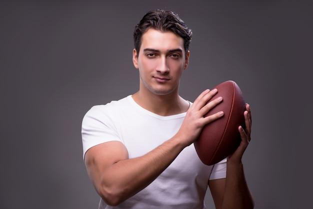 Mężczyzna z futbolem amerykańskim w sporta pojęciu