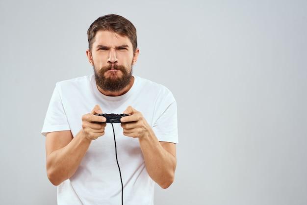 Mężczyzna z gamepadem w dłoniach grając w gry rozrywka technologia styl życia biały t-shirt jasnym tle.