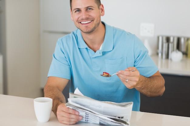 Mężczyzna z gazetą ma zboża przy stołem