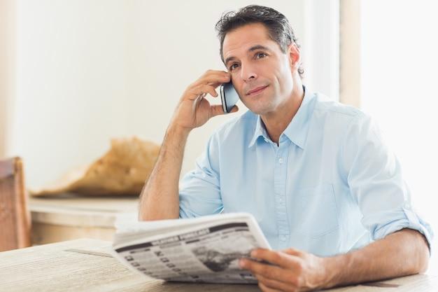Mężczyzna z gazetowym używa telefonem komórkowym w kuchni