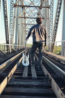 Mężczyzna z gitarą elektryczną w industrialnym krajobrazie na zewnątrz