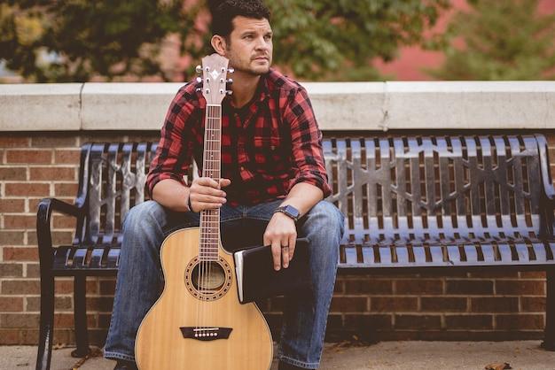 Mężczyzna z gitarą i książką siedzi na ławce w parku w słońcu