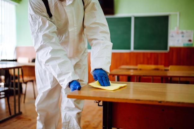 Mężczyzna z grupy dezynfekcji żółtą szmatką czyści biurko w szkole. profesjonalny pracownik sterylizuje klasę, aby zapobiec rozprzestrzenianiu się covid-19. koncepcja opieki zdrowotnej uczniów i studentów.