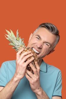Mężczyzna z grymasem i otwartymi ustami w pobliżu ananasa