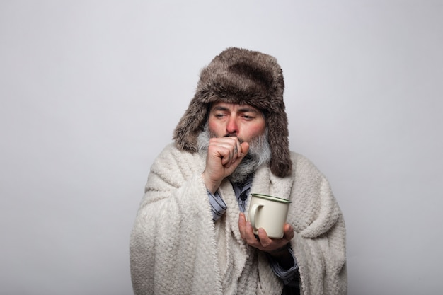 Mężczyzna z grypą i kaszlem chroniony kapeluszem i kocem