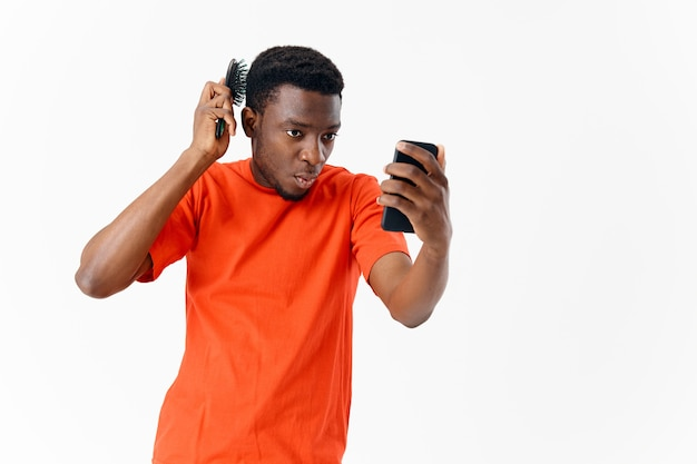 Mężczyzna z grzebieniem w dłoniach przygląda się stylizacji telefonu na głowę