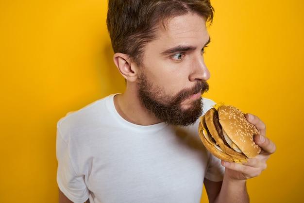 Mężczyzna z hamburgerem w rękach. nosi białą koszulkę. zbliżenie żółte tło.