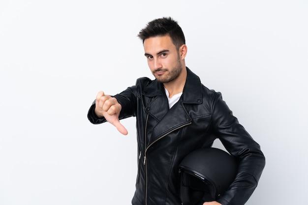 Mężczyzna z hełmem motocyklowym pokazuje kciuka puszek z negatywnym wyrażeniem
