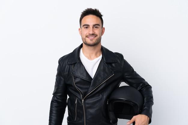 Mężczyzna z hełmem motocyklowym pozuje z rękami przy modnym i uśmiechniętym
