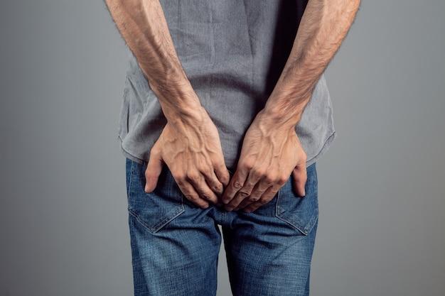 Mężczyzna z hemoroidami trzymający tyłek na szarym tle