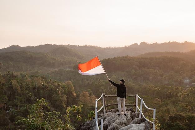 Mężczyzna z indonezyjską flaga indonesia na górze góry