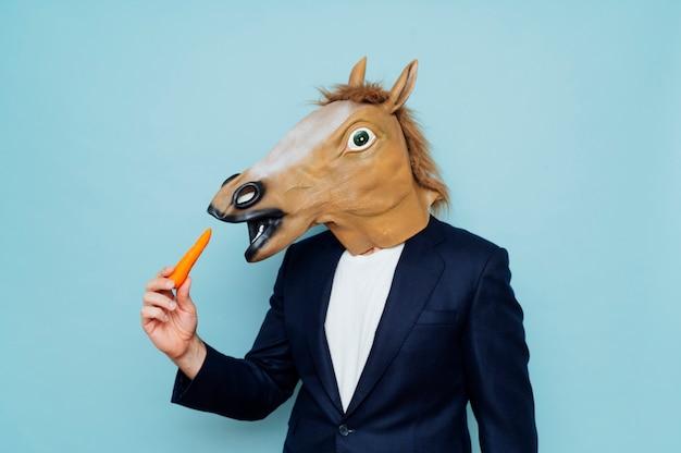 Mężczyzna z jedzącą maską konia
