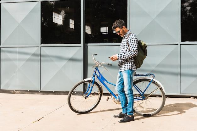 Mężczyzna z jego plecakiem używać telefon komórkowy pozycję blisko bicyklu