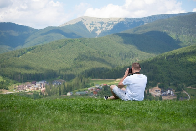 Mężczyzna z kamery obsiadaniem na wzgórzu i fotografii naturą.