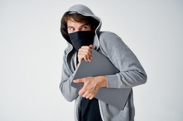Mężczyzna z kapturem na głowie, maska kradzieży laptopa, nielegalny wjazd.