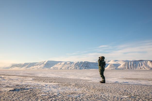 Mężczyzna z karabinem i lornetką spoglądający na arktyczny krajobraz svalbardu